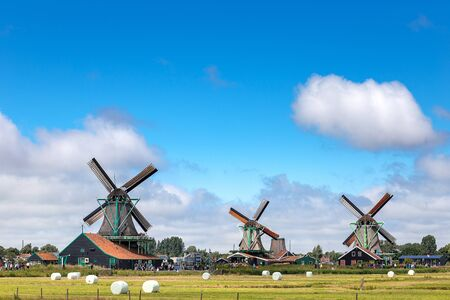 Old and classic dutch windmill in Zaanse Schans where is the famous landmark for tourist to travel in traditional and nature with canal and blue sky in north of Amsterdam, Holland or Netherlands, Europe