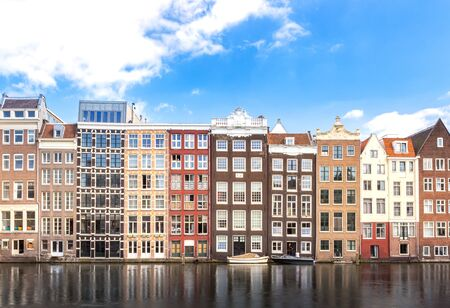 beautiful and classic building of apartment and reflection on water along river or canal for tourist, tour, cruise or ship transportation in Amsterdam in Netherlands Europe Фото со стока