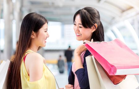 happiness couple woman, friend, smile during fashion shopping together near sale fashion shopping store and hold shopping bag and gift in hand in mall center of city