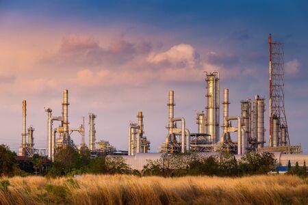 heure du coucher du soleil avec champ agricole et usine chimique usine pétrochimique et pétrolière avec réacteur et distillation en raffinerie pour processus chimique en zone industrielle