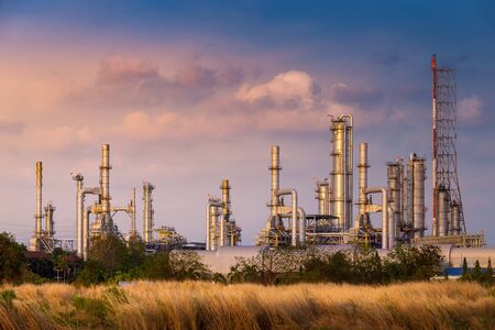 sunset time with agriculture field and chemical plant petrochemical and petroleum plant with reactor and distillation in refinery for chemical process in industrial area