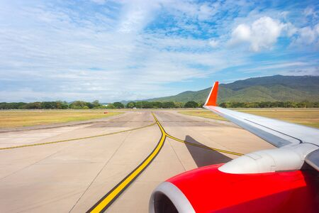 airplane window seat with red engine and wing view during landing or take off on runway, taxi way, in airport for international transportation of passenger for business and travel by air, aircraft, transportation with mountain and clear blue sky in background Standard-Bild