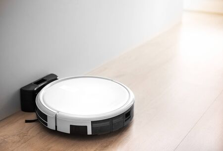 white robot vacuum machine auto clean in bedroom, livingroom of smart home and house instead of human by innovation technology for home and order by smart phone or remote