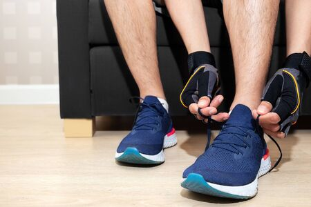 happy sport man tie shoelace of his running shoe on sofa in home living room for running, jogging, and exercise in morning in fitroom and race running track for good health during work from home period Stock Photo