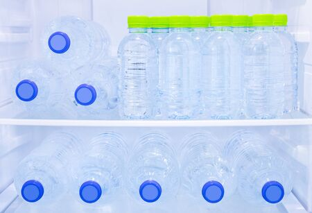many mineral fresh and clean drinking water in plastic bottle freeze in cooler shelf or refrigerator in kitchen for cool water for person who want to refresh there life after business work or thirst and after meal food
