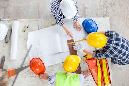 manager and engineer work as teamwork together at industrial construction site for meeting and concept plan with equipment document drawing of building with safety and design for thie job in office with happy work life Archivio Fotografico