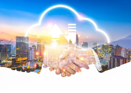 success businessman shakehand with partner business teamwork with big cloud data storage transfer online database concept of smart cyber connection technology in future and internet, with sunset and skyline