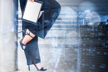 success manager business woman wear high heel and hold digital tablet with white empty screen for business communication connection technology skyline background Standard-Bild