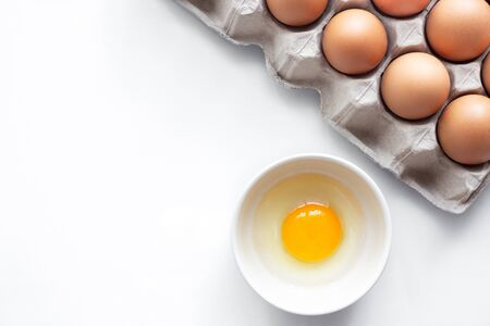 closeup of fresh chicken egg on egg box, panel, on white background with one fragile egg shell for cook for food of meal and fresh and natural egg in bowl for healthy concept