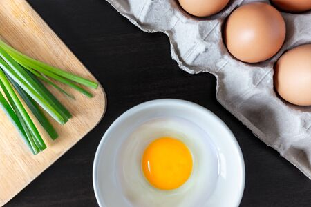 closeup of natural  spring onion on wood butcher and fresh chicken egg, protein, in bowl and group of egg in box on wooden kitchen table for healthly and delicious meal or homemade food cook concept