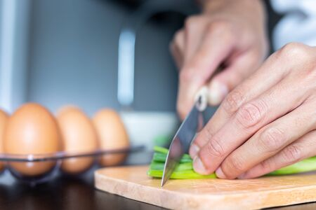 closeup of people hand and knife slice spring onion on wood butcher and fresh chicken egg in bowl and group of egg in box on wooden kitchen table for healthly and delicious meal or homemade food cook concept for family dinner menu Standard-Bild