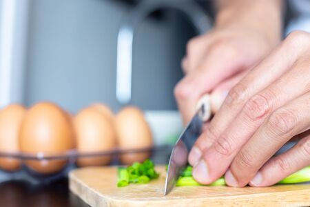 closeup of people hand and knife slice spring onion on wood butcher and fresh chicken egg in bowl and group of egg in box on wooden kitchen table for healthly and delicious meal or homemade food cook concept for family dinner menu Archivio Fotografico