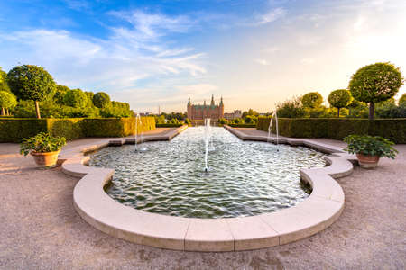 Sunset view of Frederiksbork palace castle with beautiful garden and fountain water at sunset time in Hillerod, near Copenhagen, Denmark, Europe, Scandinavia in summer