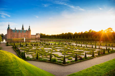 Sunset view of Frederiksbork palace castle, where is a famous landmark for travel and visit museum, with beautiful garden and fountain water at sunset time in Hillerod, near Copenhagen, Denmark, Europe, Scandinavia in summer Editoriali