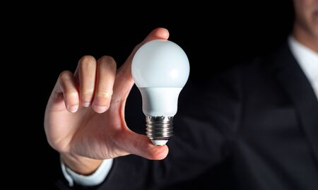 success businessman hold lightbulb for success business creative thinking idea concept with suit during work in office and innovation success energy conservation on black background Archivio Fotografico