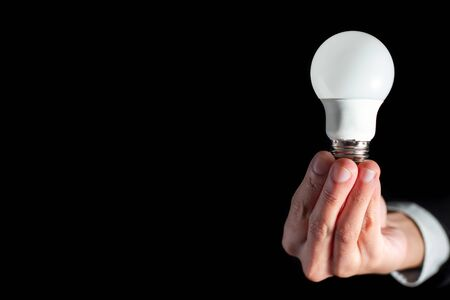 success businessman hold technology lightbulb for success business creative thinking idea concept with suit during work in office and innovation success energy conservation on black background