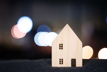 House or home wood model for family happy concept with bokeh light from modern downtown city in business movement background Banque d'images