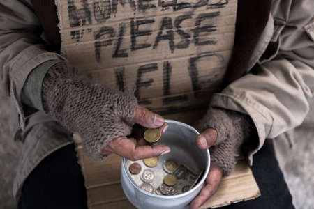 beggar homeless hold dollar money coin from his box sign of sadness unhappy from abandon and alone old man in dirty environment in business city concept