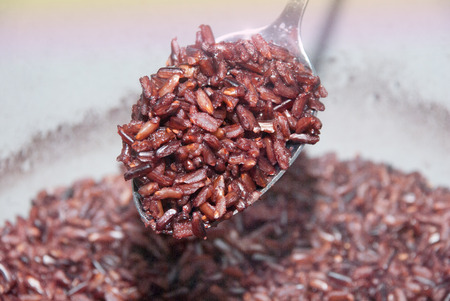 black textured background: Black rice with wooden spoon Stock Photo