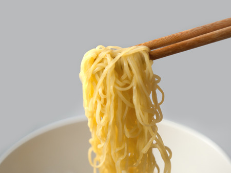 cooked instant noodle: Yellow noodles, a bowl, a cup on a white background.
