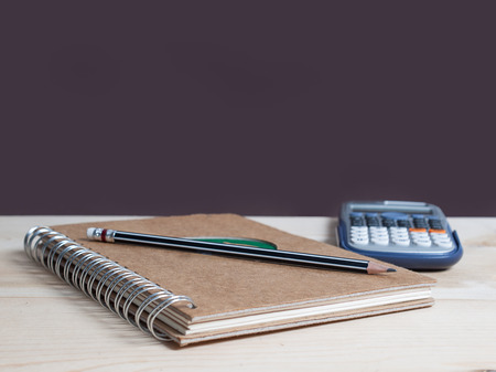 memo pad: book diary , and pencils  , on the wooden desk with copy space.