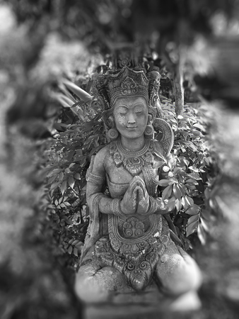 Close up of Grey Buddha statue in flower garden Stock Photo