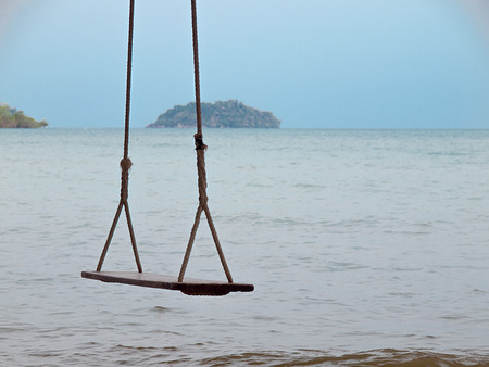 Rope swing under tree on ocean beach , Sea background. Stock Photo