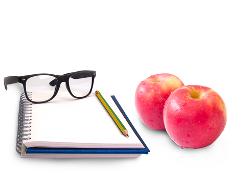 Notebook , glasses and apple fruit on white background.