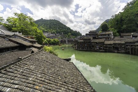 Boats surround the winding river of greenish color. Fenghuang Ancient Town, Hunan province, China 写真素材