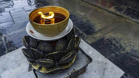 Closeup of candle in a cup shaped like flowers. Shaolin Monastery at Songshan Mountain, Henan province, China