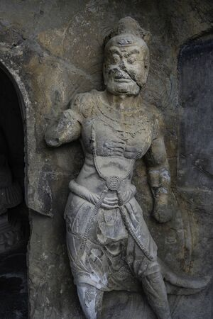 Muscular warrior carved in limestone. Figure is protecting a cave door. Wei style grotto at Longmen Grottoes, Luoyang, Henan province, China Stock Photo