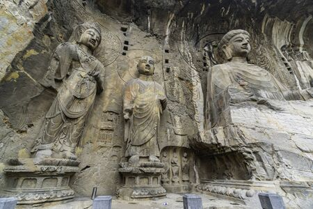Big statue made in limestone of Vairocana Buddha, monks and bodhisattvas. The main cave (Fengxiangsi Cave) of Longmen Grottoes in Luoyang. Henan province, China