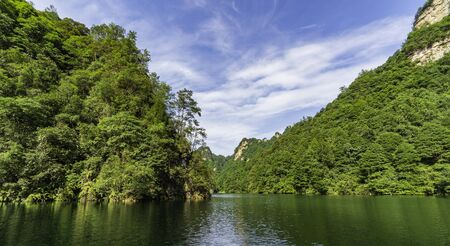 Views of a lake of calm water surrounded by dense mountains of vegetation and trees. Baofeng Lake (Bao Feng Hu) in Suoxi Valley, Wulingyuan, China