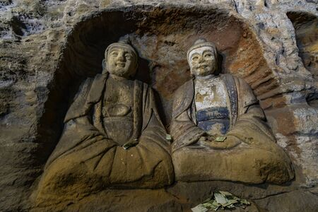 Couple of ancient painted and carved Buddha statues in a niche. World cultural heritage site and Buddhist Caves Art Treasure Houses in Yungang Grottoes near Datong, Shanxi Province, China
