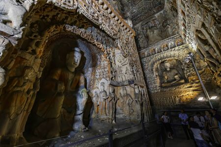 Painted caves with buddha and monk statues in niches. World cultural heritage site and Buddhist Caves Art Treasure Houses in Yungang Grottoes near Datong, Shanxi Province, China Stock Photo