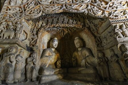Buddhist Caves Art Treasure Houses. Painted caves with hundred of ancient colored buddha and monk statues in niches. Yungang Grottoes, Datong, Shanxi Province, China
