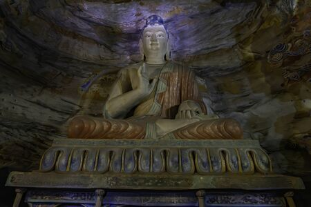 Painted statue of buddha sitting on top of an altar inside a cave. Yungang Grottoes near Datong, Shanxi Province, China