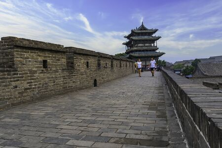 Huge old wall of the Pingyao citadel overlooking the background to the old watchtower of the entrance door. Pingyao Ancient City, Shanxi province, China