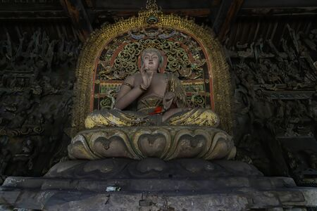 Old statue of buddha in ancient altar with carved details carved in wood. Altar figure located in Shuanglin Temple (or Zhongdu Temple), outskirts Pingyao Old City, Shanxi province, China