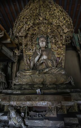 Ancient statue of buddha in ancient altar with carved details in wood. Altar figure located in Shuanglin Temple (or Zhongdu Temple), outskirts Pingyao Old City, Shanxi province, China Stock Photo
