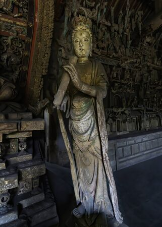 Wood carving of bodhisatta statue. Standing Avalokitesvara sculpture. Finest chinese art at Shuanglin Temple (or Zhongdu Temple), outskirts Pingyao Old City, Shanxi province, China Stock Photo