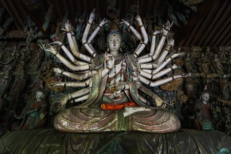 Fine ancient figure of buddhist goddess with 24 arms. Altar statue made in wood located in Shuanglin Temple (or Zhongdu Temple), outskirts Pingyao Old City, Shanxi province, China