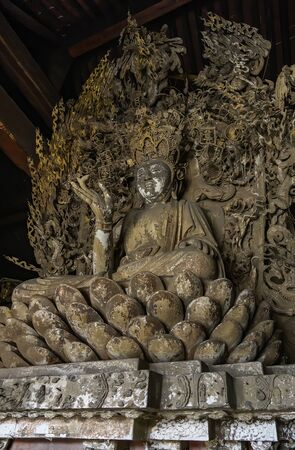 Old statue of buddha in ancient altar with carved details in wood. Altar figure located in Shuanglin Temple (or Zhongdu Temple), outskirts Pingyao Old City, Shanxi province, China