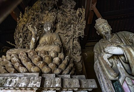 Old statue of buddha and chinese god in ancient altar with carved details carved in wood. Altar figure located in Shuanglin Temple (or Zhongdu Temple), outskirts Pingyao Old City, Shanxi province, China