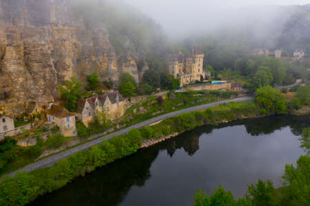 France, the picturesque village of La Roque Gageac in Dordogne covered by fog and low clouds. Dordogne river. Perigord zone, Nouvelle-Aquitaine, southwestern France.