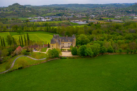 Aerial view of the Château de Montal (Castle of Montal) in spring. Castle is surrounded by beautiful green meadows Dordogne Valley, Lot department, southern France.