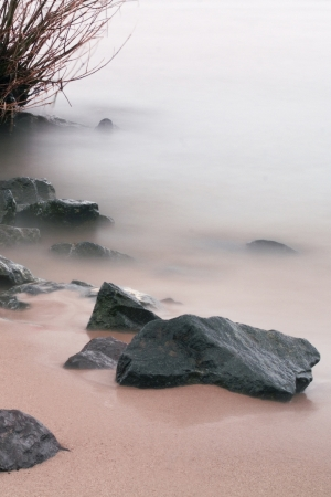rocks on the beach by a mystic fog surroundet Stock Photo