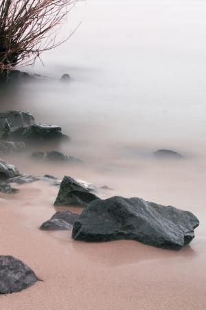 mistery: rocks on the beach by a mystic fog surroundet Stock Photo