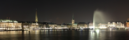 Hamburg Town Hall with Alster Fountain at night Stock Photo