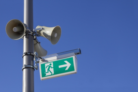 three Megaphones and a emergency exit sign mounted to a silver pole on blue skies photo